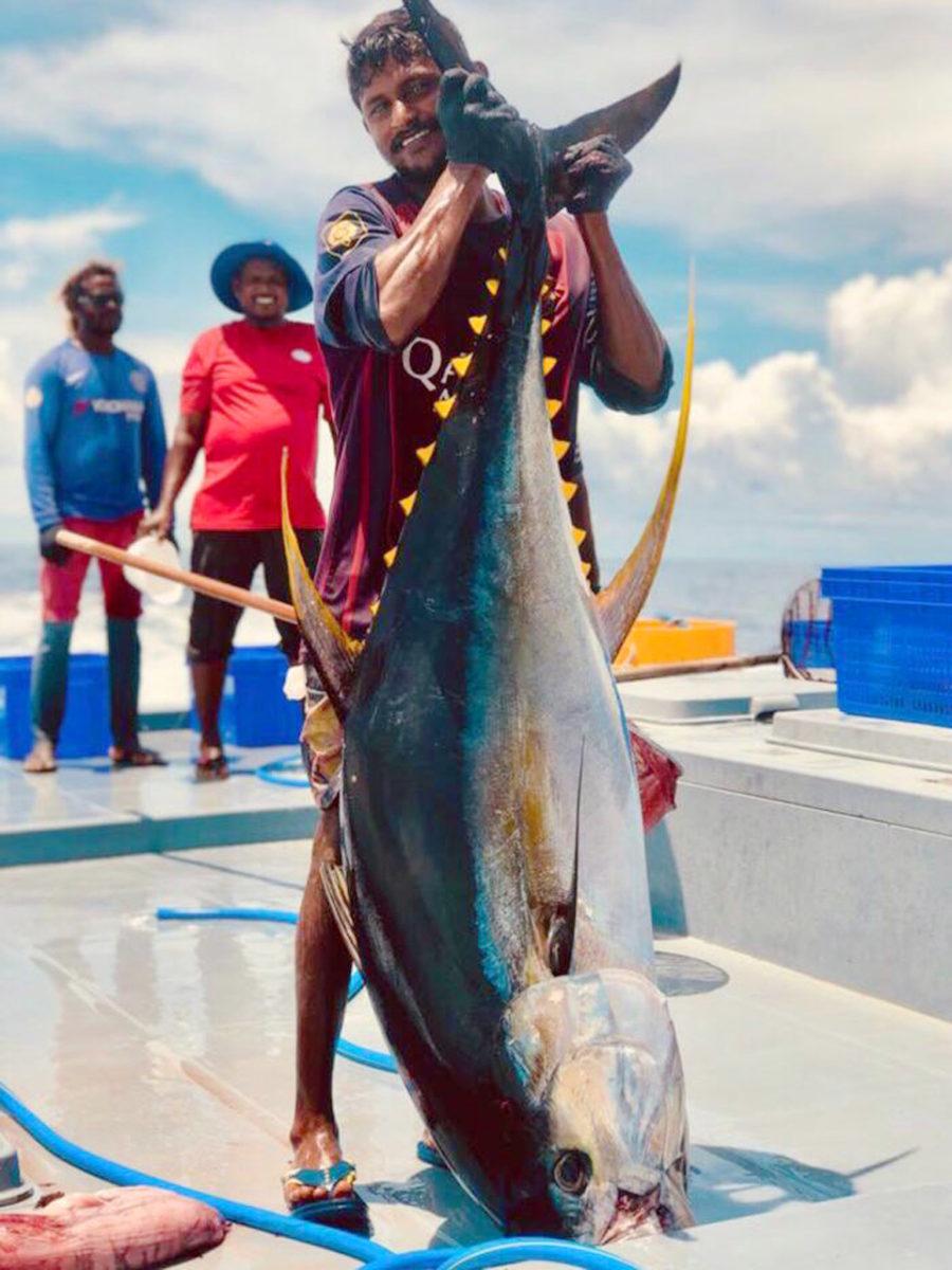 Pècheur qui tient un thon par la queue